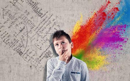 Przemyślany dzieciak przed ścianą narysowaną i podzieloną półkulami mózgu. Połowa kreatywna i połówka logiczna.