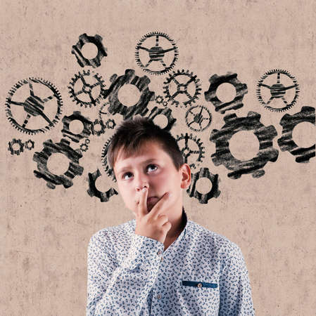 Young man thinking in front of a drawn wall with gears .