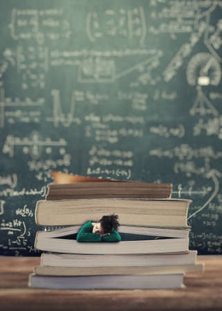Young girl sleeping between pages of a book , math formulas drawn on blackboard.Back to school concept.