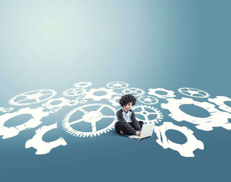 Businessman working on laptop and sitting on a drawing with engine gear wheels 版權商用圖片