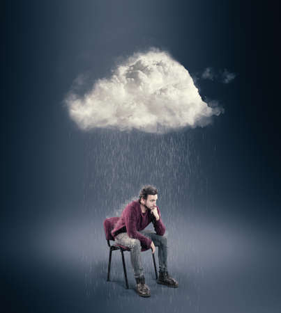 The man is sitting on a chair and thinking with a cloud over his head. Thoughtful concept