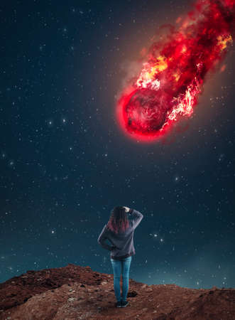 Confused woman looking up to a falling meteorite during night.
