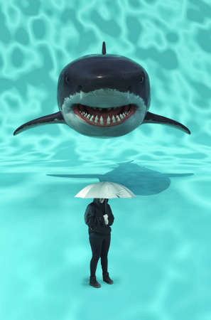 Person underwater holding an umbrella and followed by a shark.  版權商用圖片
