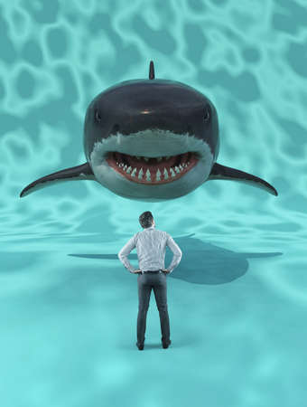 Businessman standing in front of a giant shark.