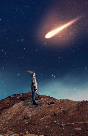 Niño mirando hacia una estrella fugaz durante la noche.