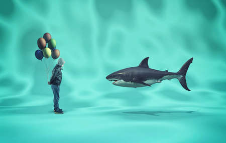Kid offering balloons to a shark underwater.