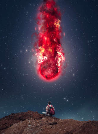 Homme avec un sac à dos regardant une météorite qui tombe pendant la nuit. Banque d'images