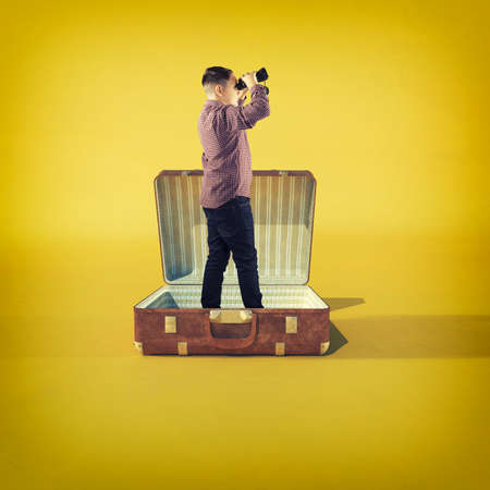 Men looks through binoculars standing in a opened luggage