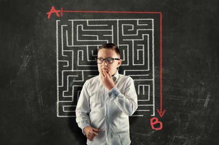 Kid solving a maze using a shortcut. Maze drawn on blackboard .