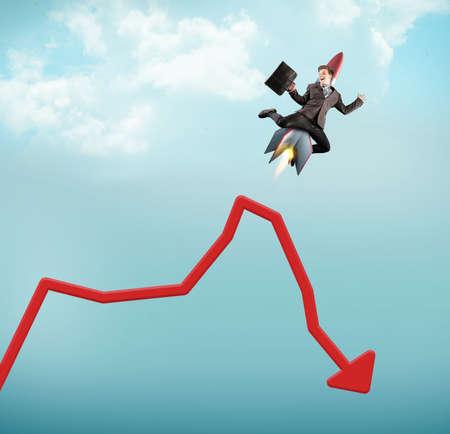Hombre de negocios volando con cohete de un gráfico decreciente.