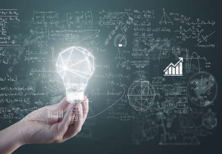 Hand holding a lightbulb in front of math formulas. Genius problem solving idea.