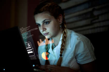 Woman working on laptop . Futuristic user interface  . High tech screens data and information .