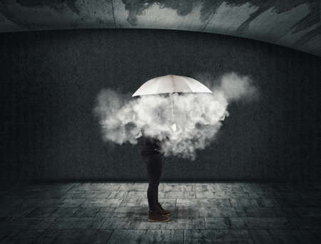 Woman holding an umbrella with a cloud inside . Useless and fail concept . Anxiety and mental illness.