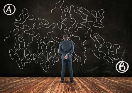 Businessman looking at a complicated path of point to point b .