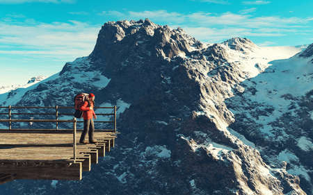 Hiker with backpack standing on a bridge in front of a mountain during winter . This is a 3d render illustration . Reklamní fotografie
