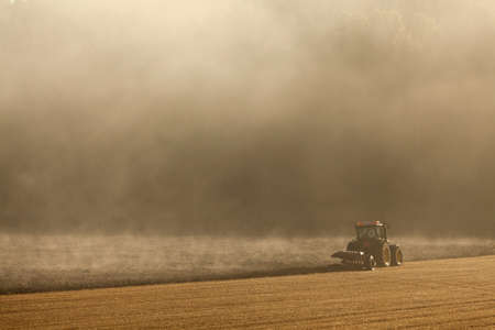 The farmer in his tractor working in the field photo