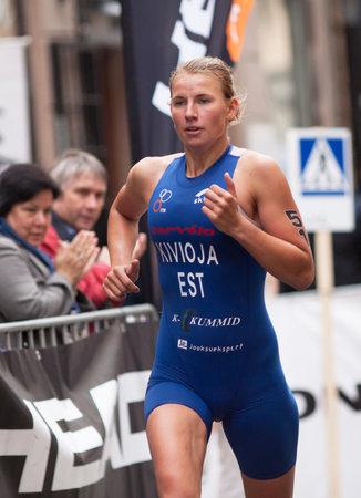 est: TOCKHOLM - AUG, 23:  World Triathlon  event Aug 23, 2014. woman running in Old town, Stockholm, Sweden. Kaidi Kivioja, EST.