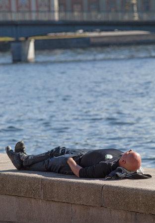 sweden resting: STOCKHOLM SEPTEMBER 03 2014.  Resting man on stone wall in the center of Stockholm.