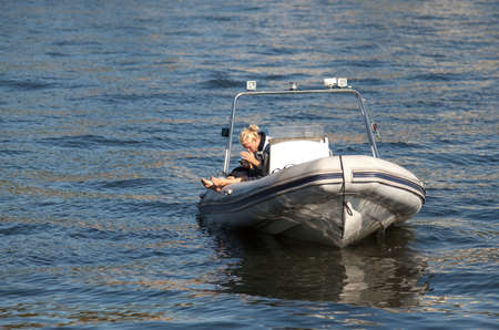 Blond man sitting in a boat and looking at his mobile phone.