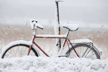 snowed: Parked and covered with snow bike at bus stop. Stock Photo