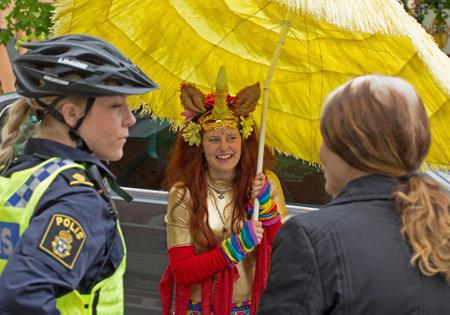 femme policier: Stockholm, Su�de - 31 MAI 2015. Peace and Love Parade. F�te de rue � Stockholm. Polici�re en casque de v�lo, de parler avec les participants du festival.