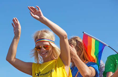 bisexual women: STOCKHOLM - AUG - 01. Stockholm Pride parade crossing the street with the name Skeppsbron 1 August 2015. Dancing girl dressed in yellow shirt and sunglasses.