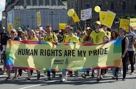 af: STOCKHOLM - AUG - 01. Stockholm Pride parade crossing the street with the name Skeppsbron 1 August 2015. Amnesty banner with the text Human rights are my pride.