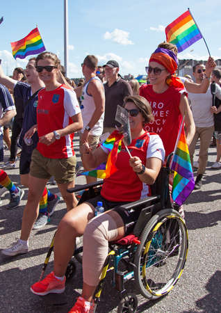 bisexual women: STOCKHOLM - AUG - 01. Stockholm Pride parade crossing the street with the name Skeppsbron 1 August 2015. Woman in wheelchair.