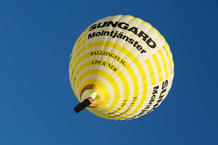 joyride: STOCKHOLM-AUG-15-2015. Yellow balloon flying over Stockholm with visitors in the basket.