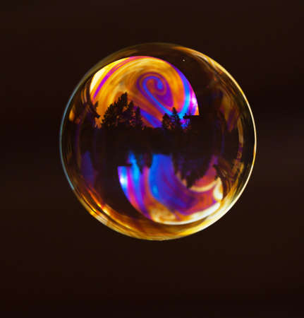 inconstant: A soap bubble with flying color reflections