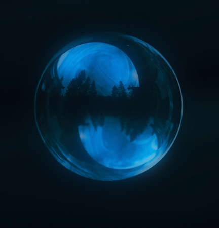 unsustainable: A  blue soap bubble with wood reflection