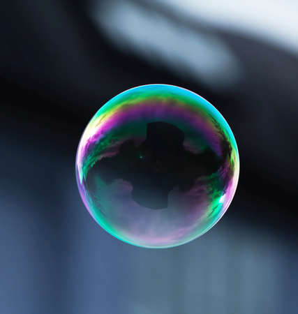 unsustainable: A flying soap bubble with reflection of a building.