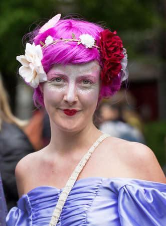 eyelids: STOCKHOLM, SWEDEN - MAY 31, 2015. Peace and Love Parade. Street party in Stockholm. Woman with bright colors, flowers and purple wig. Editorial