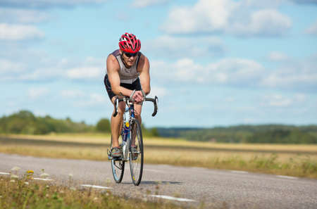 exerted: MORKO SWEDEN - AUG 29 2015: Triathlon for both exercisers and professional exerted on August 29 on an island in Sweden. Participants cycling on country. road