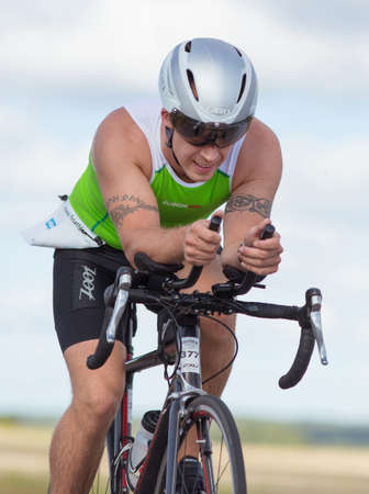 MORKO SWEDEN - AUG 29 2015: Triathlon for both exercisers and professional exerted on August 29 on an island in Sweden. Male athlete cycling on the country road at high speed.