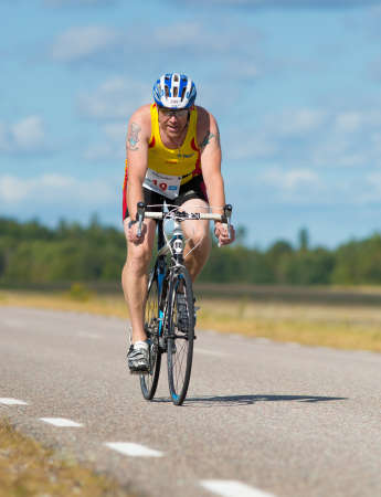 exerted: MORKO SWEDEN - AUG 29 2015: Triathlon for both exercisers and professional exerted on August 29 on an island in Sweden. Male athlete cycling on the country road.