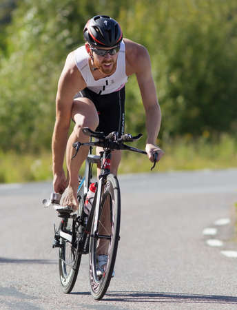 exerted: MORKO SWEDEN - AUG 29 2015: Triathlon for both exercisers and professional exerted on August 29 on an island in Sweden. Male athlete cycling on the country road and preparing for the final leg running.