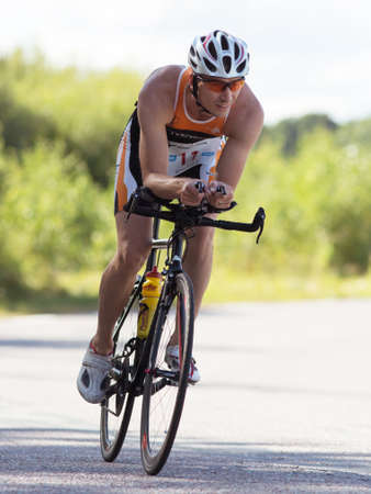 exerted: MORKO SWEDEN - AUG 29 2015: Triathlon for both exercisers and professional exerted on August 29 on an island in Sweden. Male athlete cycling on the country road at high speed.