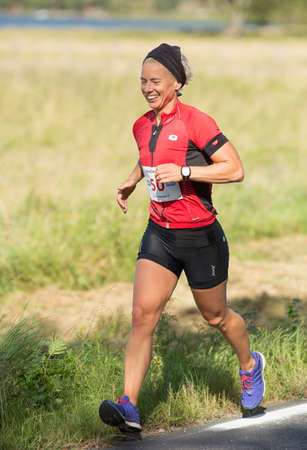 exerted: MORKO SWEDEN - AUG 29 2015: Triathlon for both exercisers and professional exerted on August 29 on an island in Sweden. Happy female runners running on light feet.