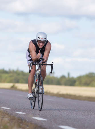 exerted: MORKO SWEDEN - AUG 29 2015: Triathlon for both exercisers and professional exerted on August 29 on an island in Sweden. Male athlete cycling on the country road at high speed and making thumbs up.