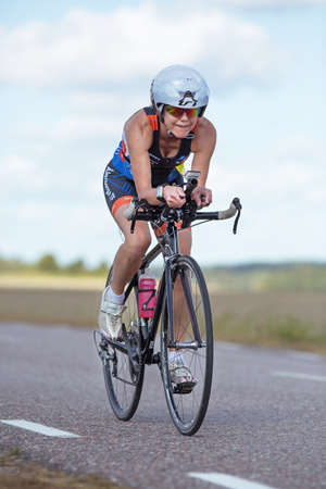 exerted: MORKO SWEDEN - AUG 29 2015: Triathlon for both exercisers and professional exerted on August 29 on an island in Sweden. Female contestants cycling on the country road at high speed.