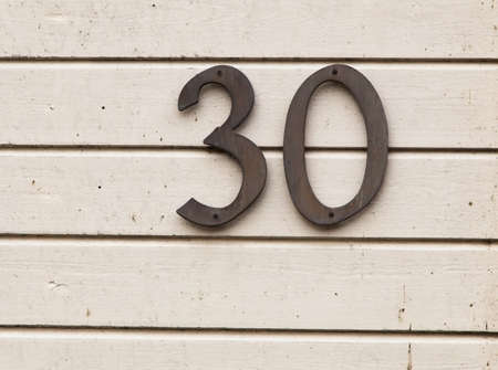 thirty: The number thirty on a light painted house wall