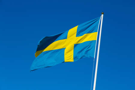 swedish: Swedish flag fluttering in the wind. Stock Photo