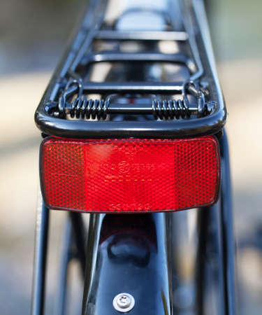 carriers: HOLO, SWEDEN, March 20. 2015. A red reflector mounted on the bike luggage carriers.
