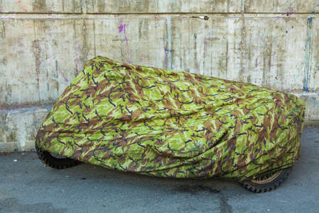 sidecar: Old motorcycle with a sidecar, hidden under a camouflage blanket