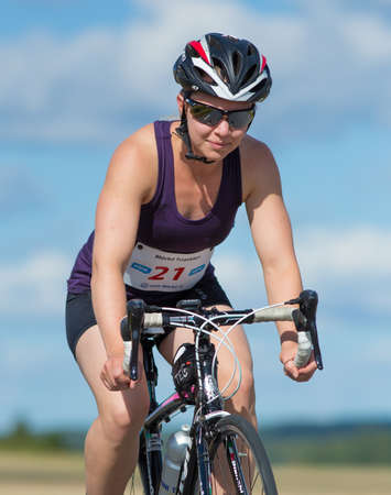 MORKO SWEDEN - AUG 29 2015: Triathlon for both exercisers and professional exerted on August 29 on an island in Sweden. Female contestants cycling on the country road at high speed.