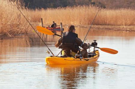 exertion: Recreational fishermen in small kayak. Stock Photo