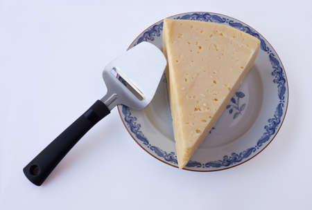 slicer: Cheese and cheese slicer, and Porcelain plate with blue border Stock Photo