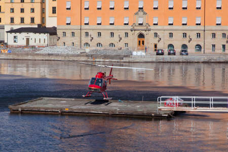 helicopter pad: STOCKHOLM SWEDEN 11 April 2016.  RED HELICOPTER lands on a helipad on the waters of Stockholm. Editorial
