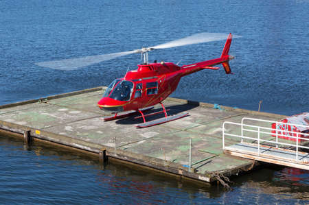 helicopter pad: STOCKHOLM SWEDEN 11 April 2016. Red helicopter flying over the waters of Stockholm.
